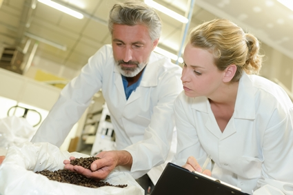 man and woman looking at coffee beans for foreign detection